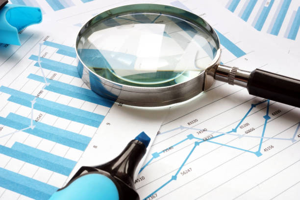 magnifying glass and financial documents. audit and accounting. - ispezione contabile foto e immagini stock