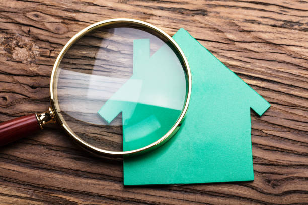 magnifying glass and green paper house - examining stock photos and pictures