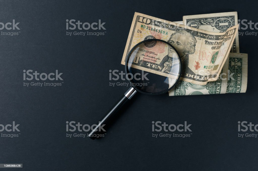 Magnifying glass and money on black background. Paper currency....