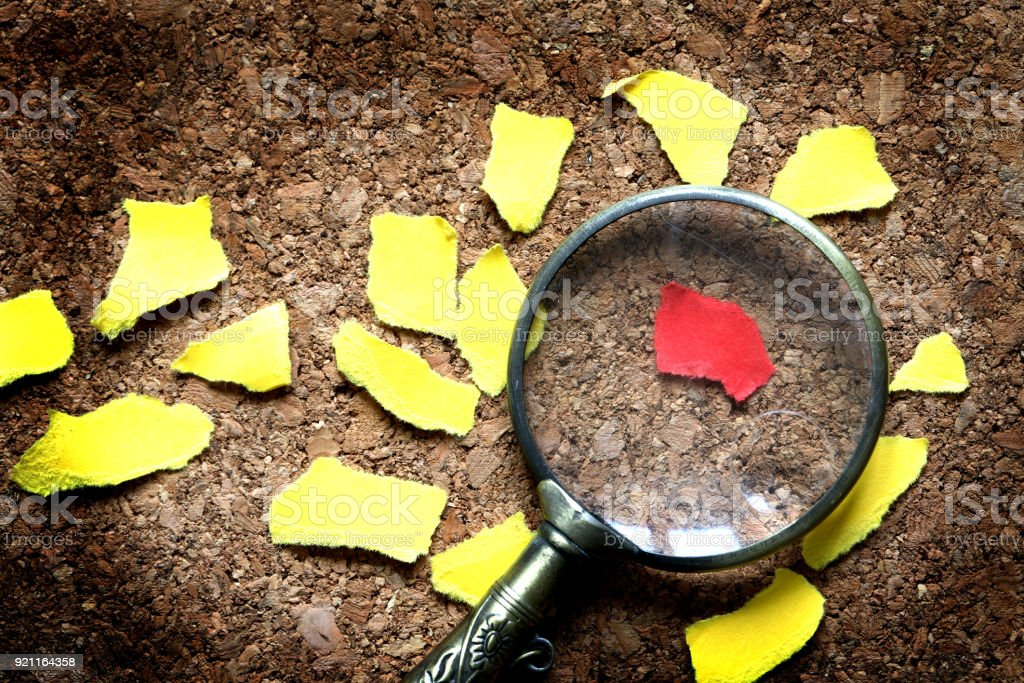 Magnifying Glass And Paper Scraps stock photo