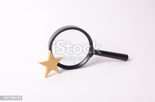 Magnifying glass and wooden golden star on a white background. Find information and things, special search capabilities. High level of service, excellent result. Search engines.