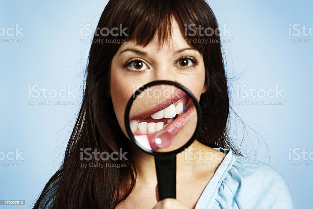 Magnifying glass distorts mouth of cute young woman bizarrely stock photo