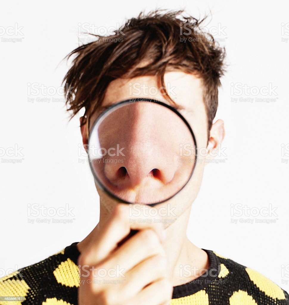 Magnifying glass enlarges young man's nose dramatically stock photo