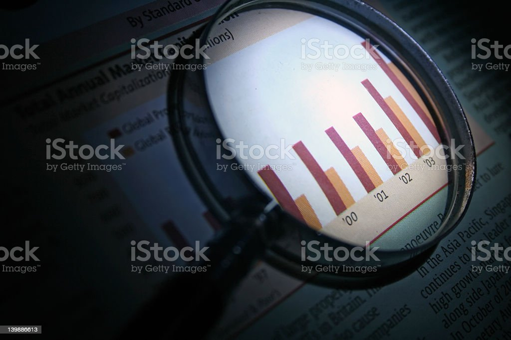 Magnifying glass enlarging a graph analyzing business royalty-free stock photo