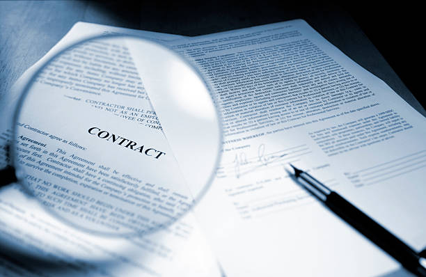 Magnifying Glass Examining Signed Legal Contract A close up blue toned image of a magnifying glass held out in front of page in a legal contract document. Sheets of paperwork are on a wooden desk with a ink pen close to a signed page. Contract text and signature are fake. Shot with  shallow depth of field with focus on the word 'Contract'. low scale magnification stock pictures, royalty-free photos & images