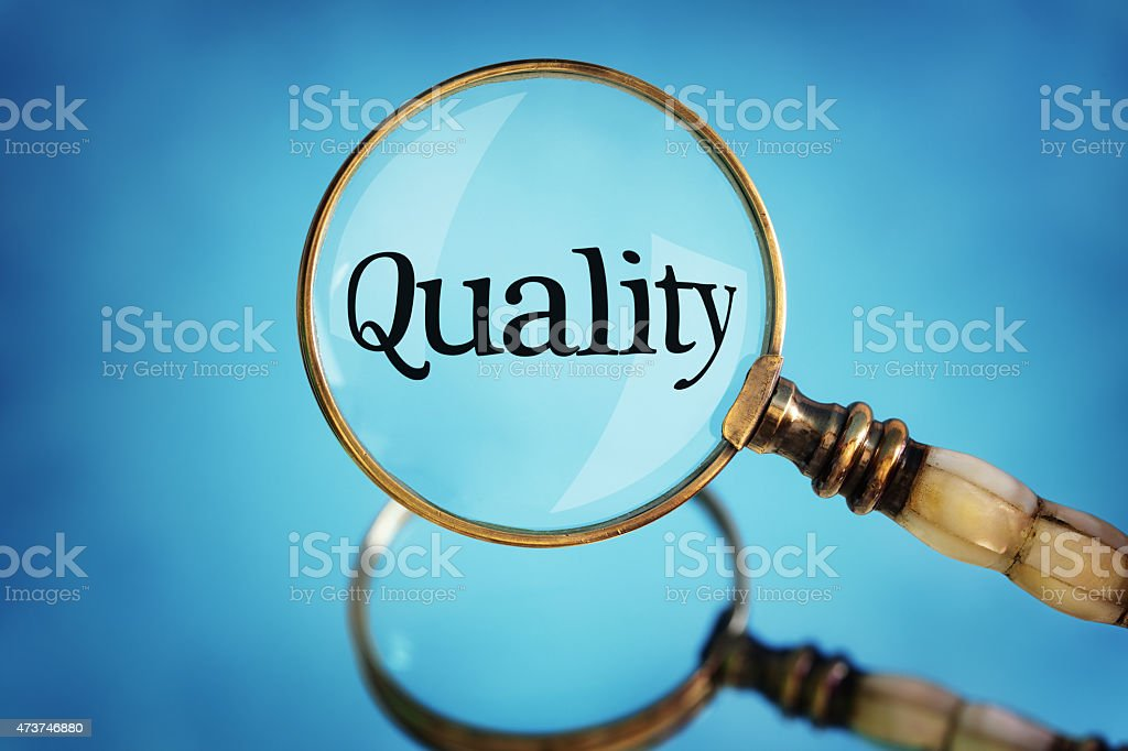 Magnifying glass focus on word quality stock photo