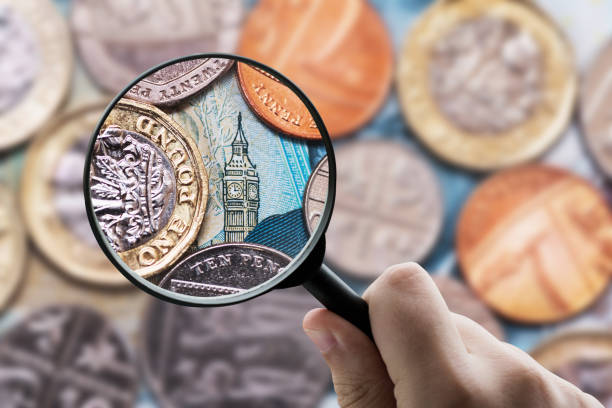 Magnifying glass focusing Great Britain Pound (GBP) currency stock photo