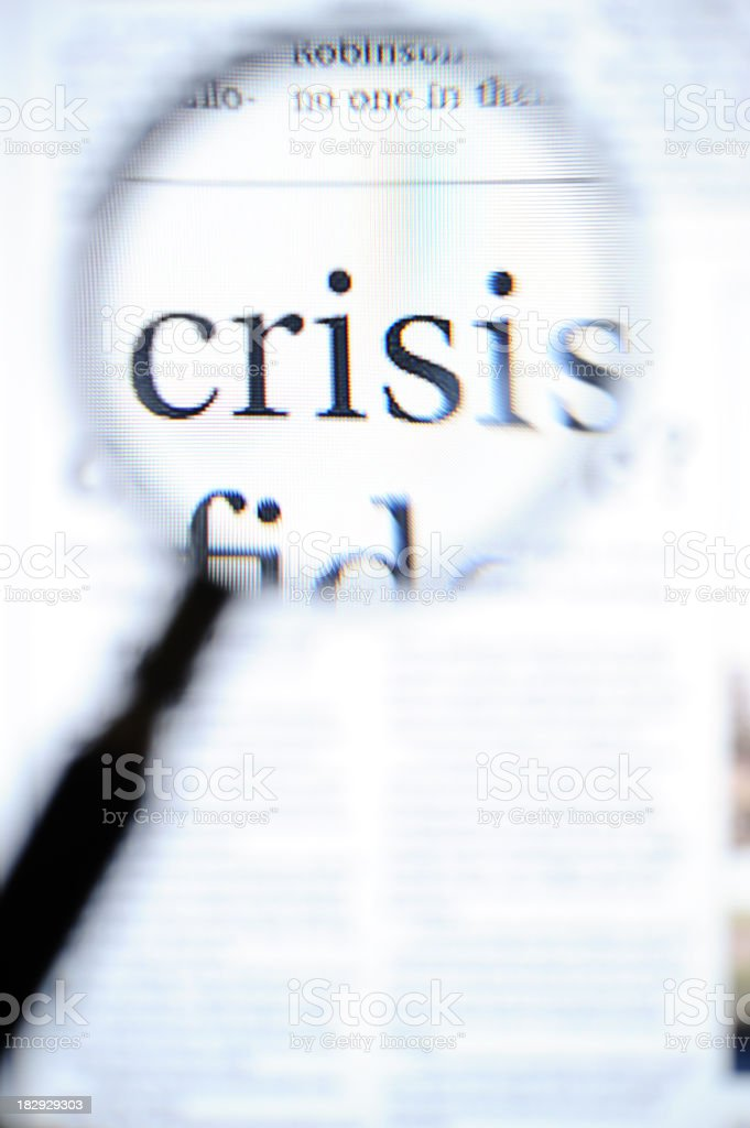 Magnifying glass focusing on crisis headlines royalty-free stock photo
