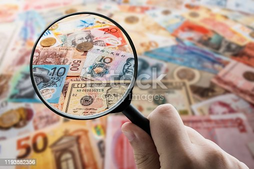A magnifying glass focusing on paper currency from diverse countries