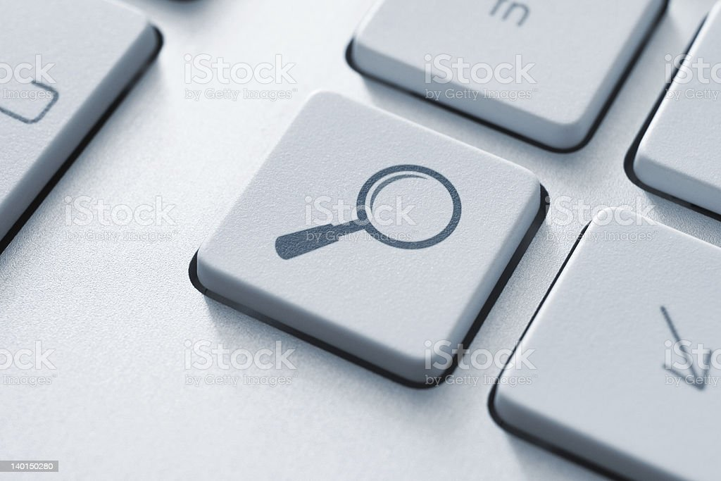 Magnifying glass graphic as search button on white keyboard royalty-free stock photo