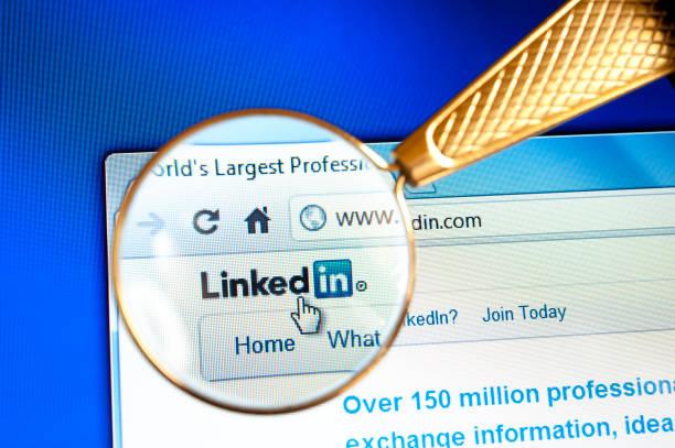 magnifying glass held over linkedin website - linkedin bildbanksfoton och bilder
