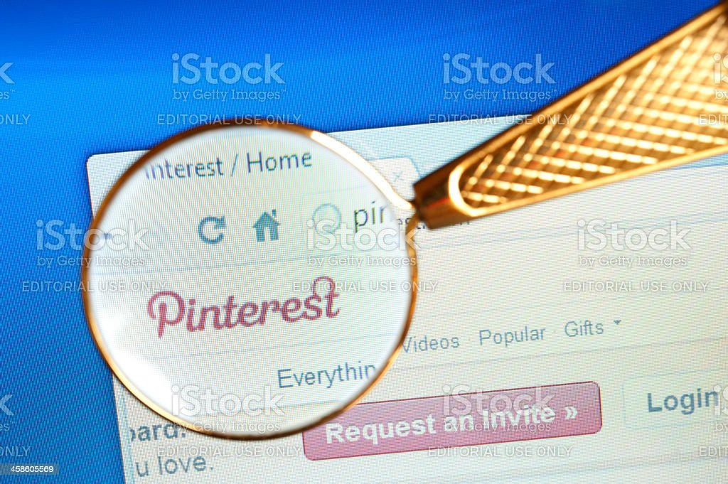 Magnifying glass held over Pinterest website royalty-free stock photo