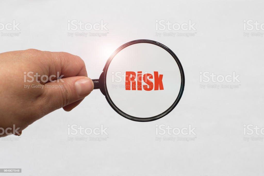 放大鏡在手和風險詞在白色背景 - 免版稅分析圖庫照片