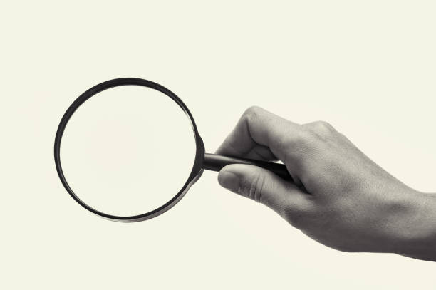 Magnifying glass in woman hand. Black and white. stock photo