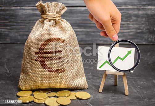 Magnifying glass is looking at a bag with euro money and green arrow up on the chart. The concept of increasing profits and revenues, increasing capital and increasing the efficiency of a business.