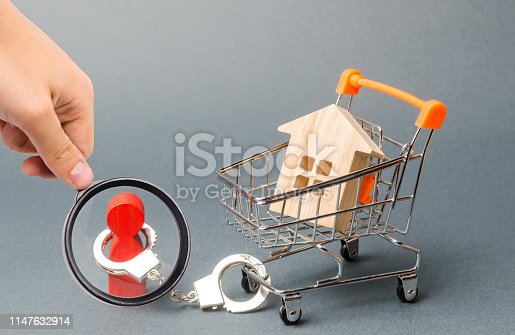 1067846662 istock photo Magnifying glass is looking at a person is handcuffed to a house on a supermarket cart. Financial dependence, unavailable housing for young families. The concept of a large debt on a loan or mortgage. 1147632914