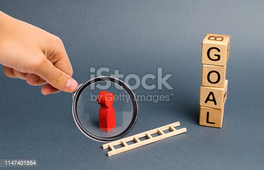 Magnifying glass is looking at a red figure of a man stands near fallen ladder and a tower of cubes with an inscription goal. achieving the goal, subject to the application of all the efforts, desires