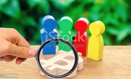 istock magnifying glass is looking at Four multi-colored figures of people surround a bitcoin figure. Conceptual conduct of activities around cryptocurrency and blockchain technology. Selective focus 1134953609