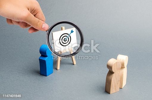 istock Magnifying glass is looking at leader explains employee tactics of advertising targeting. Training, briefing. Search strategies for effective advertising campaigns, customer reach. Business processes 1147401545
