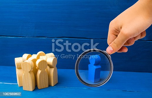 1007383644istockphoto Magnifying glass is looking at the crowd of wooden figures of people stand distantly and look at the blue man. The person tries to establish contact with the group. Good business leader 1062669802
