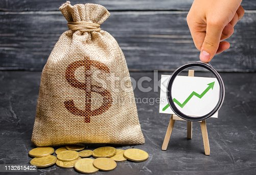 Magnifying glass is looking at the green arrow up on the chart and a Bag with money. concept of increasing profits and revenues, increasing capital and increasing the efficiency of a business. Success