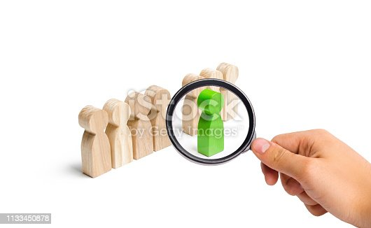 483424715 istock photo Magnifying glass is looking at the green figure of a man comes out of the line of people. concept of success and improvement in work, the universal recognition of efficiency and leadership qualities. 1133450878