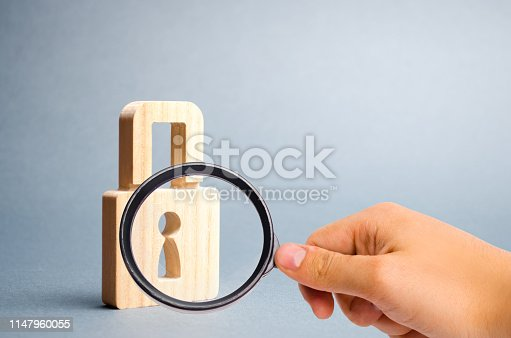 istock Magnifying glass is looking at the padlock on a gray background. information safty. concept of the preservation of secrets, information and values. Protection of data and information. Selective focus 1147960055