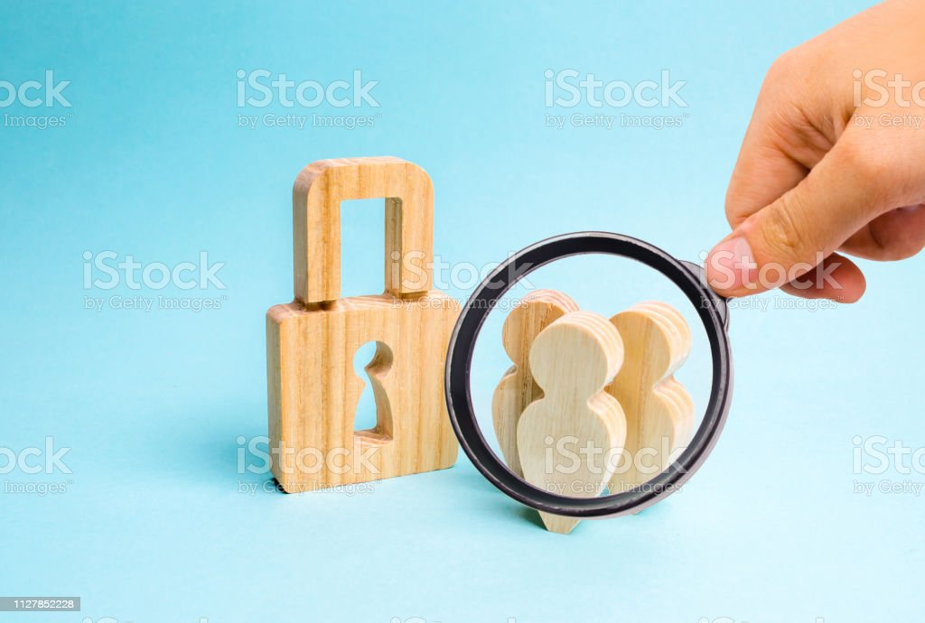 Magnifying Glass Is Looking At The Safety And Alarm System Security Service Wooden People With Padlocks Three People With A Lock Security And Safety Collateral Loan For A Mortgage Stock Photo