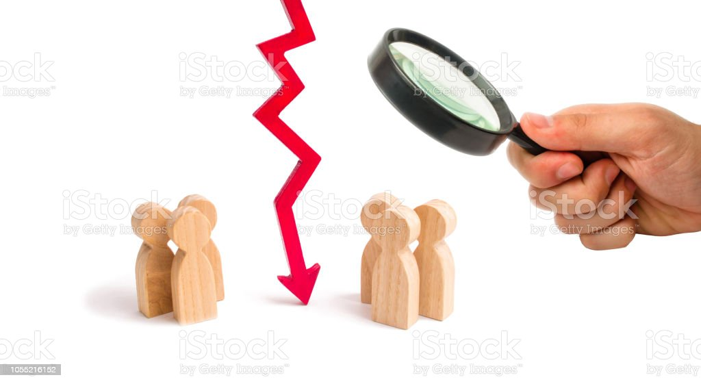 Magnifying glass is looking at the wooden red chart arrow down divides the two groups discussing the case. breaking ties. Contract break, conflict of interests. Negotiations of businessmen. stock photo