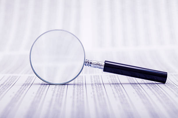 Magnifying glass laid on side atop coded papers stock photo