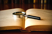 istock Magnifying glass laid on the open pages of an old book 106512664