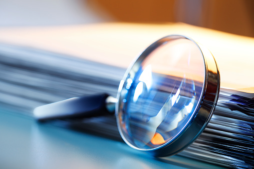 A magnifying glass leans against a thick stack of papers. Photographed with a very shallow depth of field.
