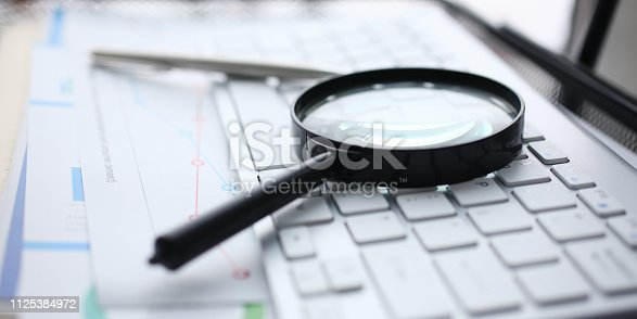 istock Magnifying glass lies on white keyboard on 1125384972