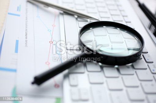 istock Magnifying glass lies on white keyboard on 1125384974