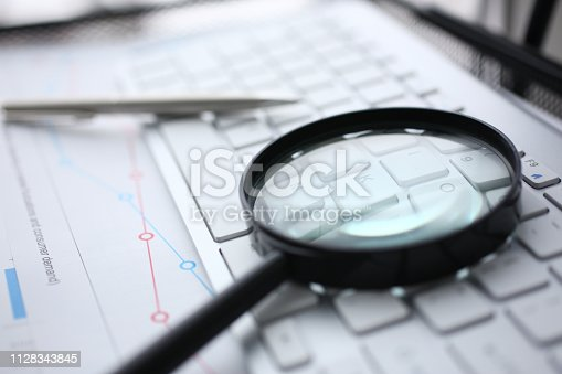 istock Magnifying glass lies on white keyboard on 1128343845
