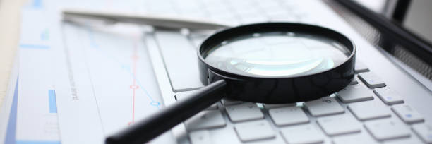 Magnifying glass lies on white keyboard on stock photo