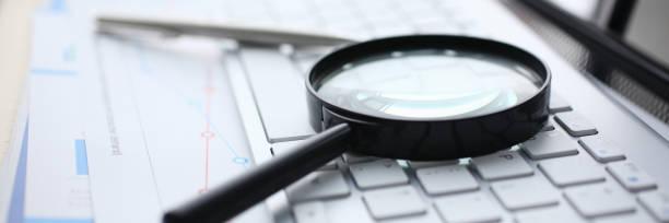 magnifying glass lies on white keyboard on - ispezione contabile foto e immagini stock