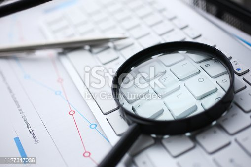 istock Magnifying glass lies on white keyboard 1127347036