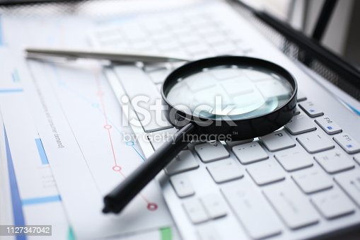 istock Magnifying glass lies on white keyboard 1127347042