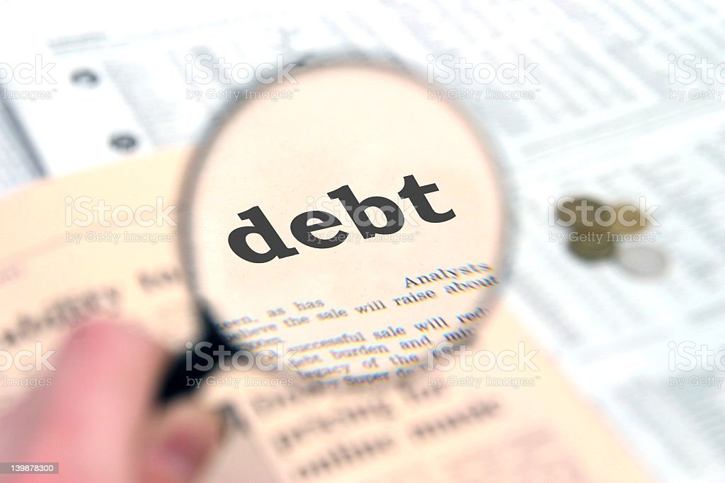 A magnifying glass magnifying the word debt royalty-free stock photo