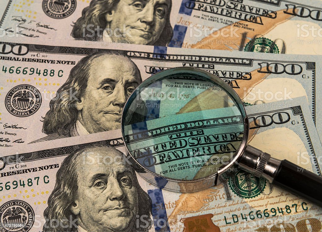 Magnifying glass on a background of money. stock photo