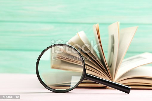 istock Magnifying glass on a pink wooden table 520501218