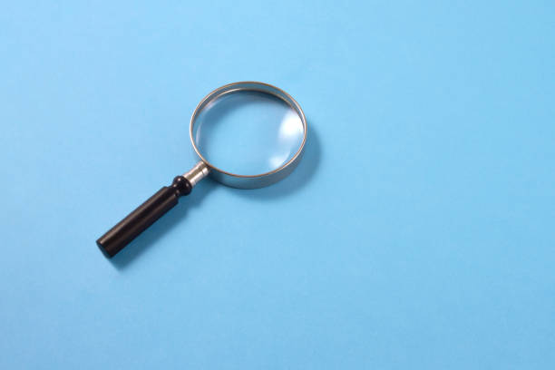 Magnifying Glass on Blue Background stock photo