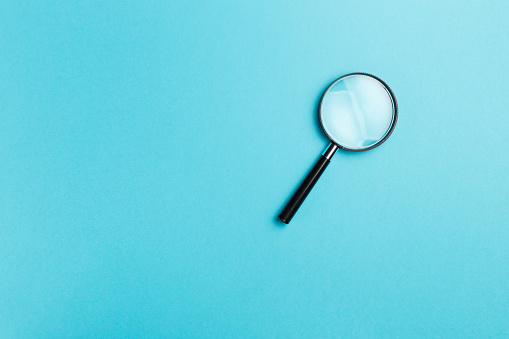 Magnifying glass on blue background. Top view. Flat lay. Copy space. Minimal creative concept. Blue background in pastel colours