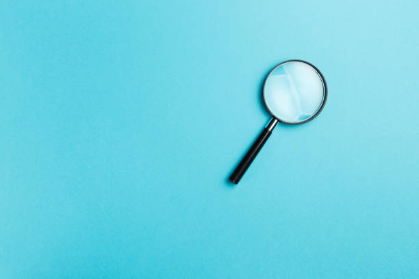 Magnifying glass on blue background. Top view. Flat lay. Copy space. Minimal creative concept. Blue background in pastel colours stock photo