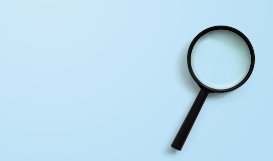 istock Magnifying glass on blue colour background with copy space. Searching information data concept 1160661180