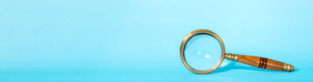 Magnifying glass on blue with copy space Old magnifying glass on a blue background. Space for copy. low scale magnification stock pictures, royalty-free photos & images