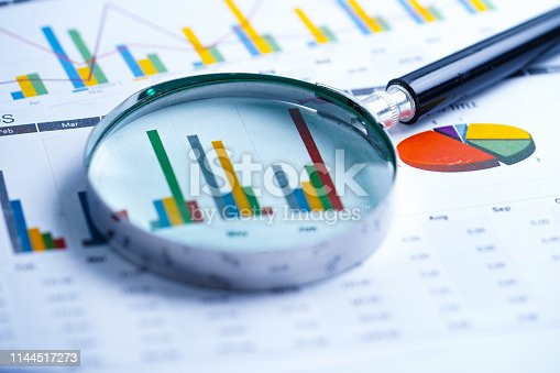 istock Magnifying glass on charts graphs spreadsheet paper. Financial development, Banking Account, Statistics, Investment Analytic research data economy, Stock exchange trading, Business office company meeting concept. 1144517273