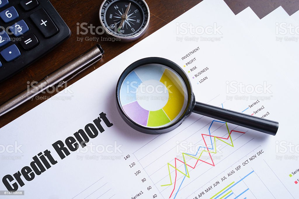 Magnifying glass on colourful pie chart with 'Credit report' text stock photo