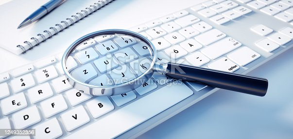 Magnifying glass lying on a white computer keyboard - Searching Information Concept